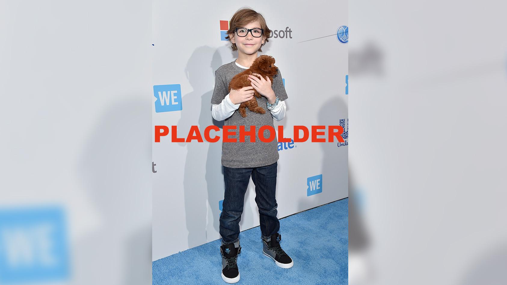 Jacob Tremblay holding a dog.